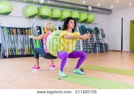 Two young women doing squat exercises standing back to back with a Swiss ball between them. Female athletes working-out in a gym