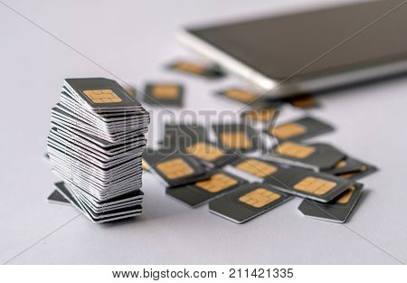gray SIM cards are collected in a pile next to the scattered other SIM cards, in the background the phone