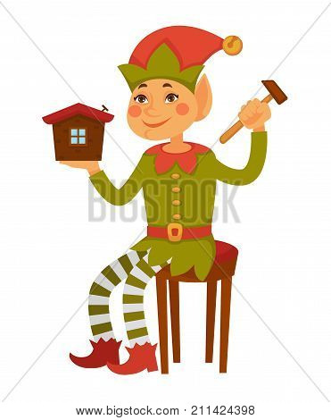 Elf in cone hat with bell on end and striped leggings sits on stool and builds toy house isolated cartoon flat vector illustration on white background. Fairy character create presents for Christmas.