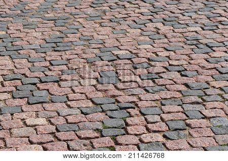 Street paved with cobblestone. Urban stone paving stones. Stone road texture. Ancient cobblestone road. Abstract background of old cobblestone pavement. Stone pavement texture. Granite cobblestoned pavement background.