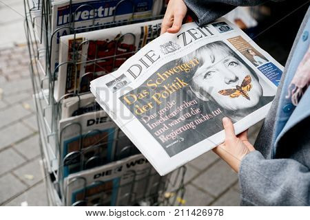 STRASBOURG FRANCE - OCT 28 2017: Woman reading buying German Die Zeit newspaper at press kiosk featuring Angela Merkel and tilte The Silenece of Politics