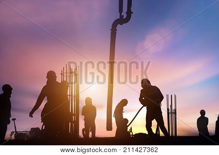 silhouette construction worker Concrete pouring during commercial concreting floors of building in big construction site and Civil Engineer or Construction engineer inspec work