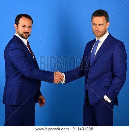 CEOs shake hands on blue background. Business and compromise concept. Businessmen wear smart suits and ties. Men with beard and serious faces make deal or agreement