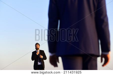 Man with beard and serious face looks forward at colleague in foreground close up. Managers wear smart suits and ties on blue sky background. Business and success concept. Businessman adjusts tie