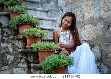 Pretty woman in ethnic Mediterranean traditional costume sitting on stone stairs.