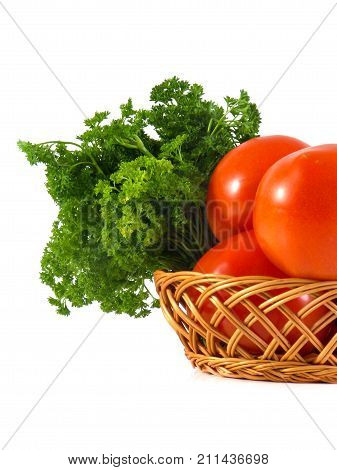 Tomato and parsley in wooden branch basket isolated on white background