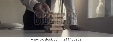 Businessman Building Tower Of Wooden Bricks With A Bright Light Flare