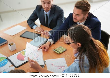 Team of young managers discussing project in office