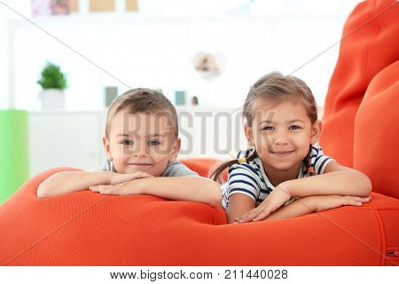 Cute boy and girl lying on bean bag cushion indoor