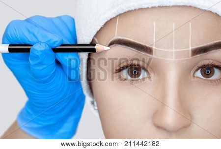 Permanent Make-up For Eyebrows Of Beautiful Woman With Thick Brows In Beauty Salon. Closeup Beautici