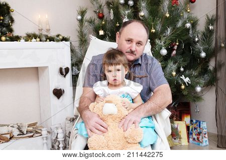 grandfather and granddaughter portrait in Christmas interior. Little girl sitting behind older father with Teddy bear next generation concept