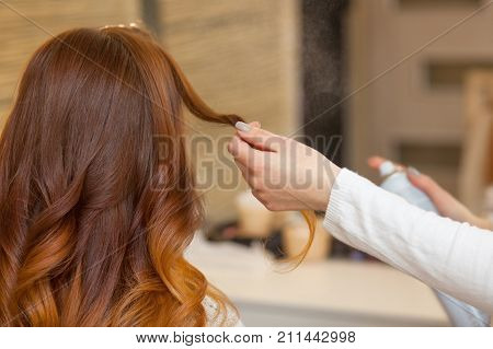 Hairdresser Combing Her Long, Red Hair Of His Client And Sprinkles Hairspray In A Beauty Salon. Prof