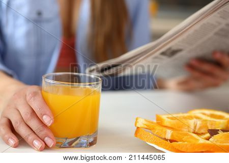 Young beautiful attractive girl in the kitchen reading a newspaper with news during breakfast and drinking orange juice holding a glass in her hand