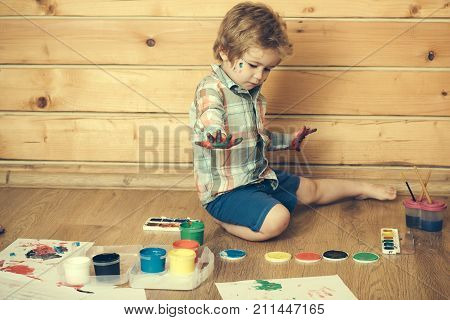 Child with colored hands gouache paints and drawings. Imagination creativity and freedom concept. Kid learning and playing. Boy painter painting on wooden floor. Arts and crafts.