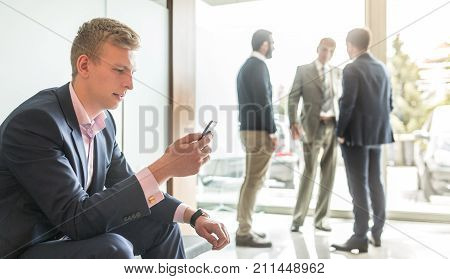 Businessman using smart phone while sitting and waiting in office building lobby. Business people talking in background.