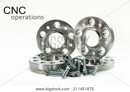 Metal mold of flange spacers and bolts on white background with superscription-CNC operations. Milling and lathe industry. Metal engineering. Horizontal indoors closeup image.