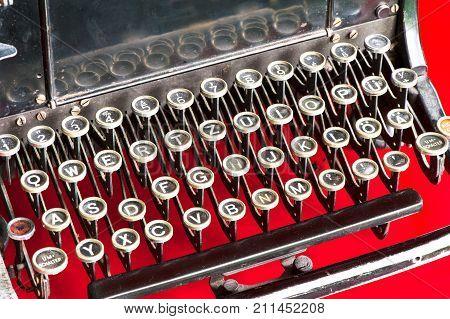 Old retro black metallic typewriter with antique round keys. Horizontal indoors colored closeup image.