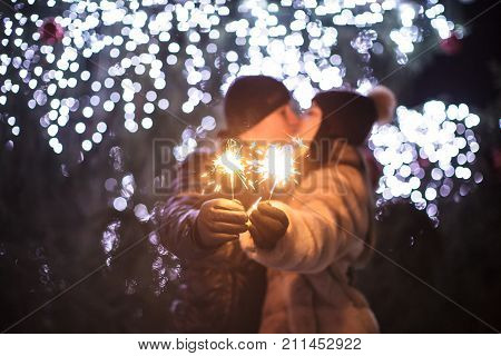 Loving couple with sparkling bengal light kissing near a Christmas tree
