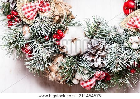 Red and white Christmas wreath with bows and cotton flowers