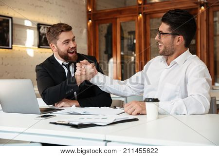 Two young handsome satisfied business partners in formalwear shaking hands in the office