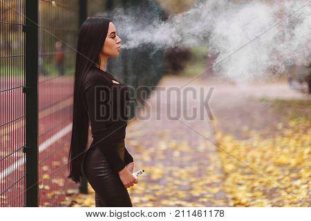 Sexy Woman Vaping Electronic Hookah Outdoor In Autumn. Vape Goodies