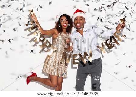 Photo of african excited happy young loving couple wearing christmas hats standing isolated over white background wall. Looking at camera drinking champagne holding happy new year garland.
