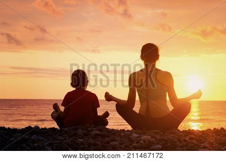 Mom And Son Meditate On The Beach In Lotus Position. View From The Back, Sunset, Silhouettes