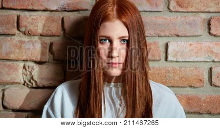 Closeup portrait of sad young ginger-haired woman looking at camera.