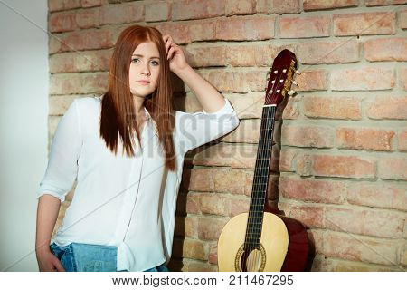 Young ginger girl leaning against wall having guitar.