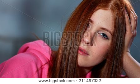 Portrait of wild ginger woman looking at camera, half face covered by hair.