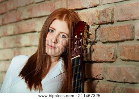 Portrait of young ginger girl with guitar.