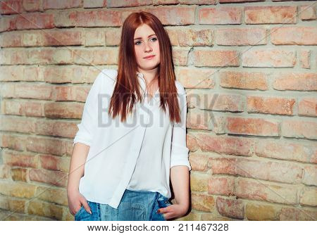 Daydreaming young ginger girl standing against brick wall.