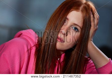 Closeup portrait of young ginger woman looking at camera with hand in hair.