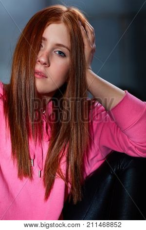 Closeup portrait of attractive young ginger woman looking at camera hand in hair.