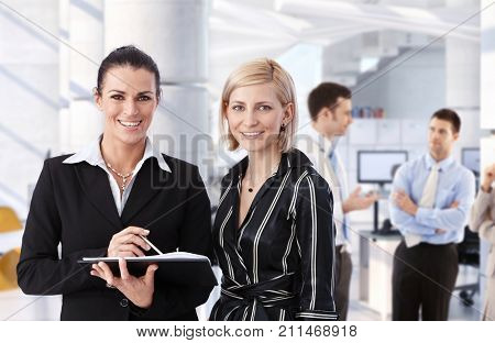 Happy mid adult caucasian business people at office meeting. Businesswomen smiling, looking at camera, with personal organizer in hand.