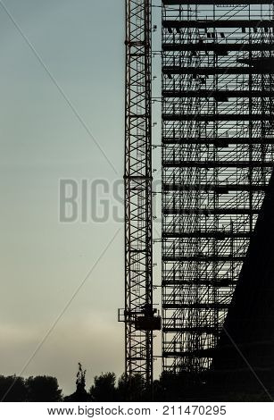 silhouette of scaffolding, working at building construction, profile sunset light structure of scaffolding and cranes