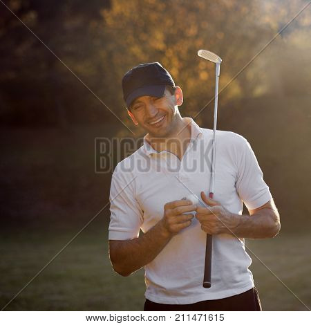 The golfer is laughing with closed eyes with golf ball and putter on autumn nature background.