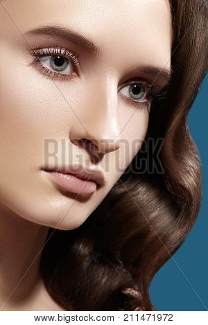 Glamour Woman Model with Fresh Daily Make-up. Wavy Hairstyle. Shiny Hair smooth clean Skin natural Makeup. Strong shape of eyebrows