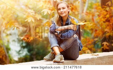 Nice female in bright sunny day sitting in the park and enjoying beautiful autumn nature and wonderful weather, with pleasure spending weekend outdoors