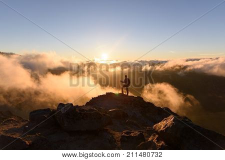Inspiration theme of man standing on top of a cliff with rolling clould. Mount Rainier National Park Washington at sunset