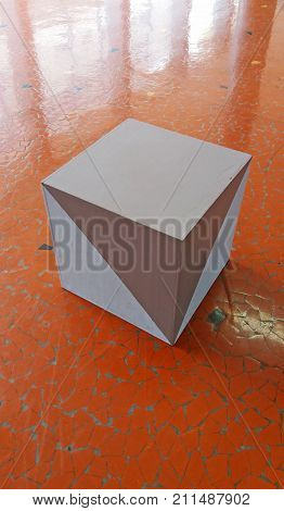 Isolated gray cube on the red floor