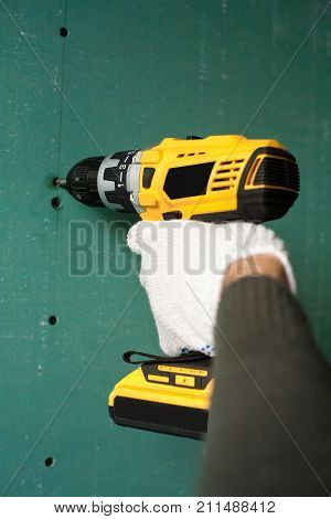 interior house alterations works Drywall Construction worker holding the hand drill electric screwdriver