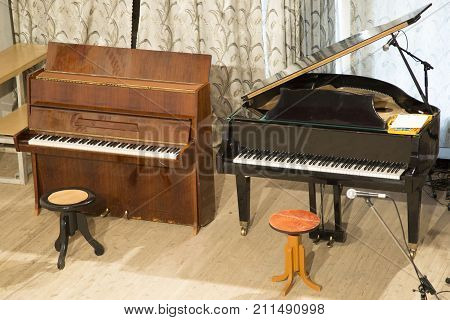 Piano and grand piano. On an empty stage in the theater on the floor there are old pianos and a piano without people