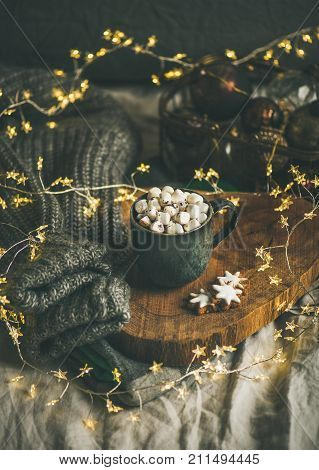 Christmas or New Year winter hot chocolate with marshmallows and cookies in black mug over wooden board served in bed with holiday light garland, blanket and gray sweater, selective focus, copy space