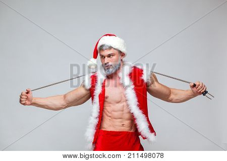 Sport, activity. Sexy Santa Claus with skipping rope. Young muscular man wearing Santa Claus hat demonstrate his muscles. on a homogeneous gray background.