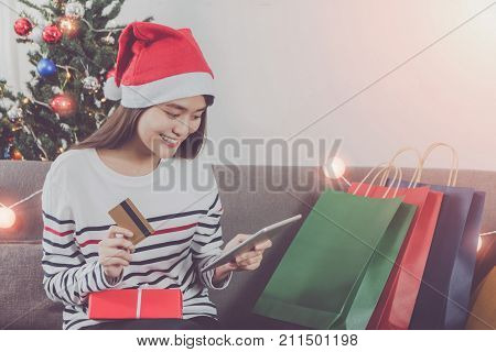 Young beautiful Asian woman shopping with credit card in Christmas holiday.Sitting with shopping bag and wearing Christmas hat with smiling face in room with Christmas tree decoration background.