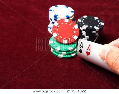 Pair of aces in a poker game. Poker chips cards and red cloth. The concept of luck in the game.