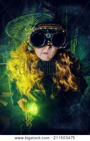 Happy Halloween. Cute child girl in witch costume is in a witch's lair. Cute funny witch girl wearing steampunk glasses.
