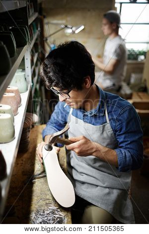 Young man in apron sitting by his workplace and hammering nails into sole of footwear workpiece