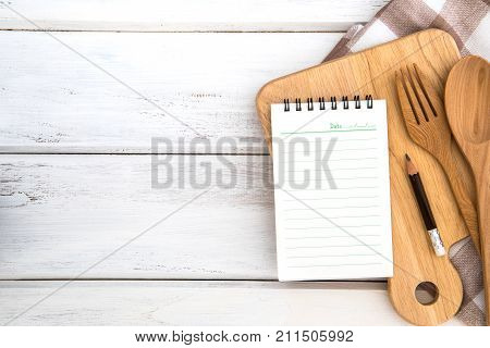 Notepad on chopping board with wooden fork and spoon on white table recipes food or diet plan for healthy habits shot note background concept